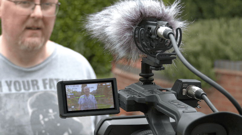 A camera mounted shotgun mic on top of a video camera showing talent on screen