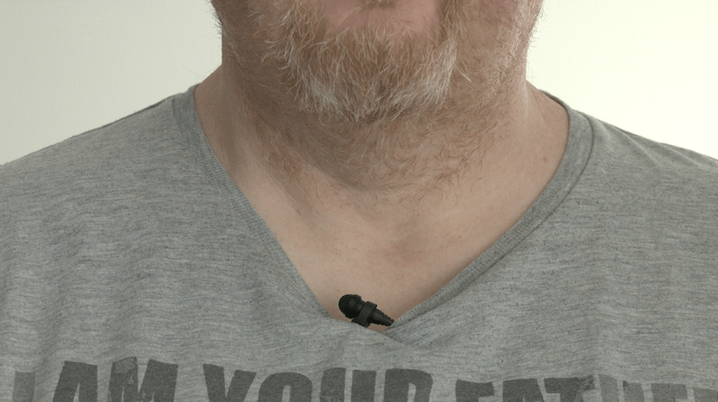 A Sennheiser ME2 lavalier mic placed on someone's clothing just below their chin.